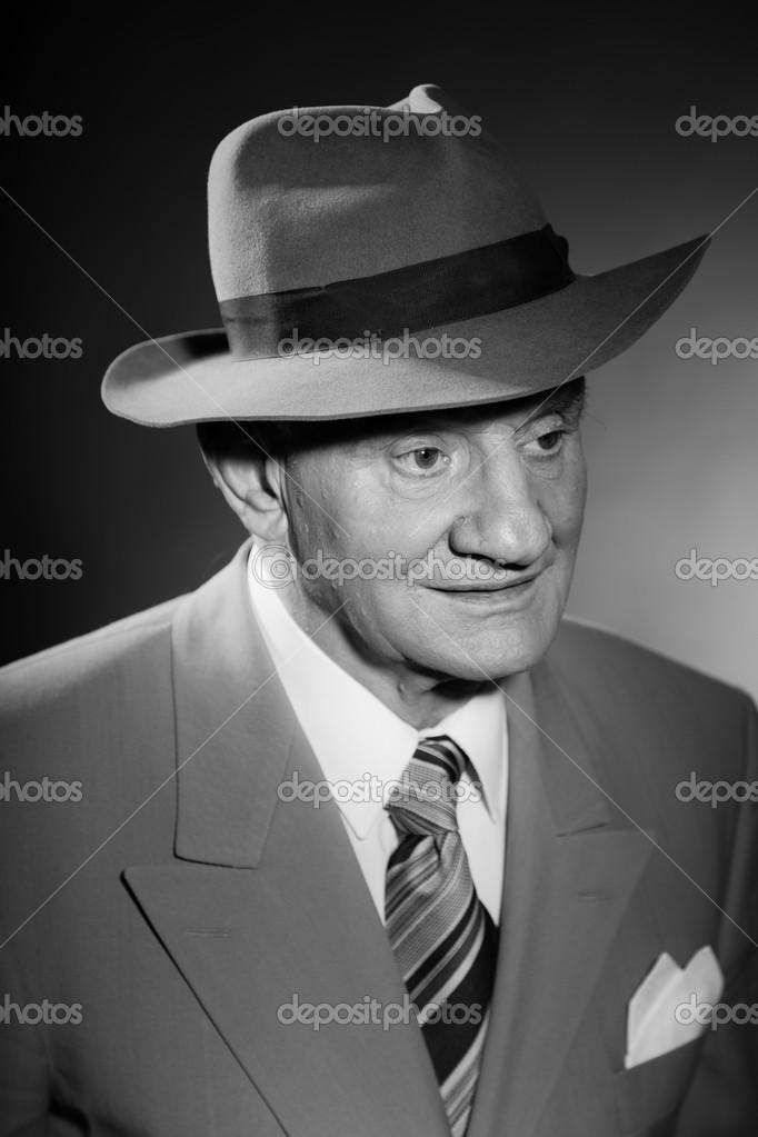 Hombre vintage glamour Senior vistiendo traje y corbata y sombrero. blanco  y negro studio le disparó. Mira gángster. aislado — Foto de ysbrand 14fbf084bee