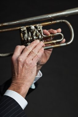 Closeup of senior male hands playing trumpet.
