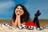 indisches Mädchen mit langen Haaren in Rot am Strand im Sommer