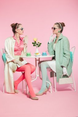 Two girls blonde hair fifties fashion style drinking tea.