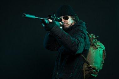 Sniper with beard in black holding gun. Studio shot.