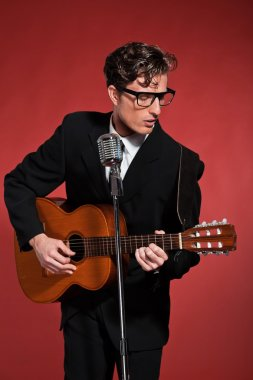 Retro fifties musician with glasses playing acoustic guitar. Stu