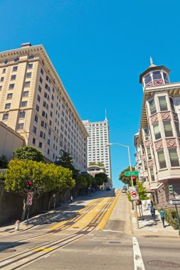 Streets and houses of San Francisco. Blue sky. Rails of cable ca