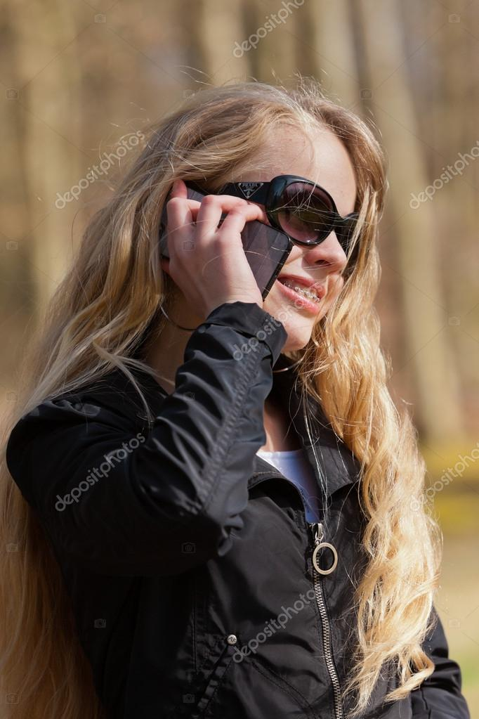 Young blonde girl with sunglasses in park calling with cellphone