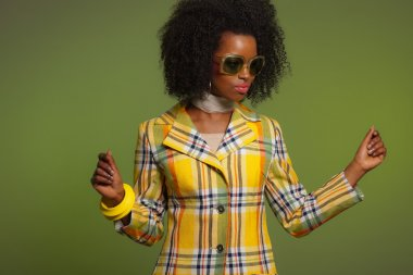 Dancing retro 70s fashion african woman with sunglasses. Yellow