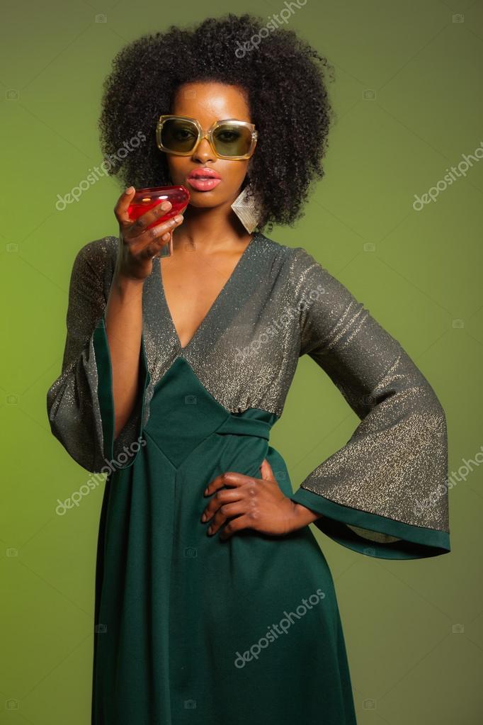 94b65608900128 Retro 70s afro mode vrouw met groene jurk en oranje cocktai — Stockfoto