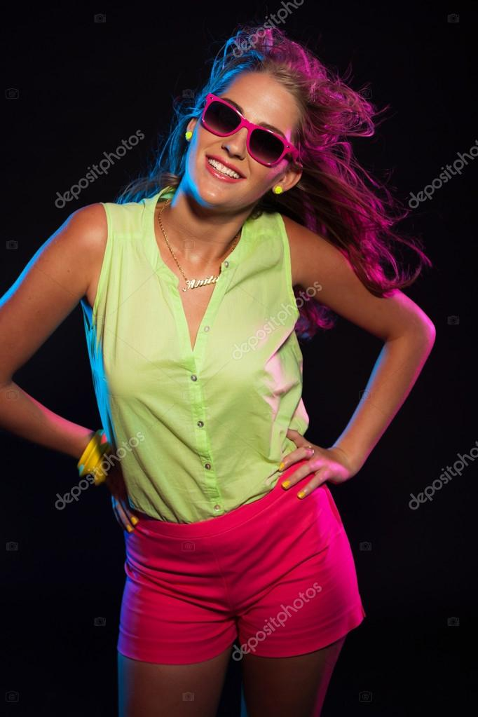 77a86a6c798 Sexy retro 80s fashion disco girl with long blonde hair and pink sunglasses.  Black background.