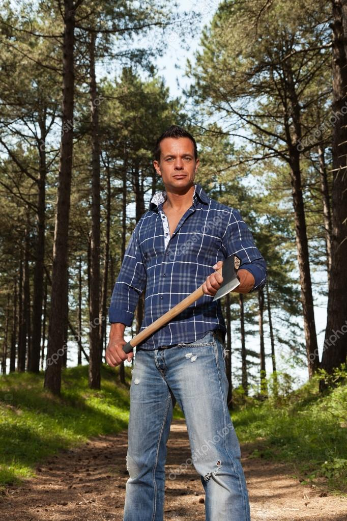 6ec07c3c Vacker stark lumberjack man med yxa. klädd i blå skjorta. stående i skogen  — Foto av ...