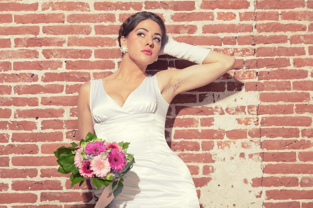 Vintage romantic sensual bride against old brick wall. Urban environment.