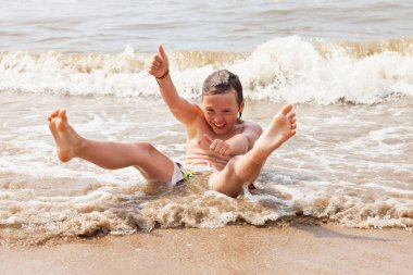 Kid boy having fun at the beach in the waves of the ocean.