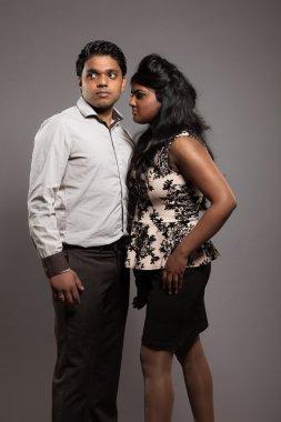 Fashionable passionate indian couple. Studio shot against grey.