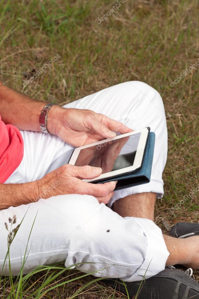 Close-up of hands of senior retired man sitting with tablet outd