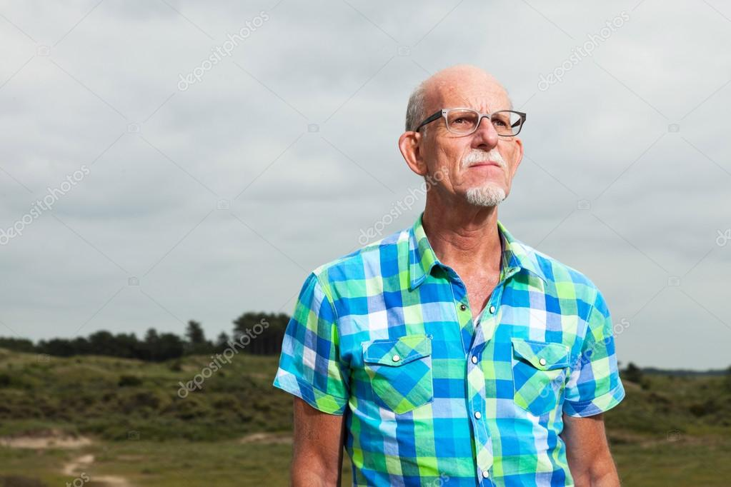 Retired senior man with beard and glasses outdoors in grass dune
