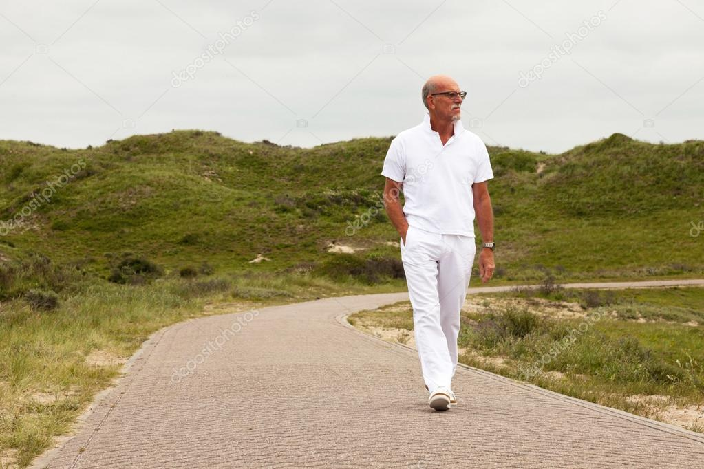 Retired senior man with beard and glasses walking outdoors in gr