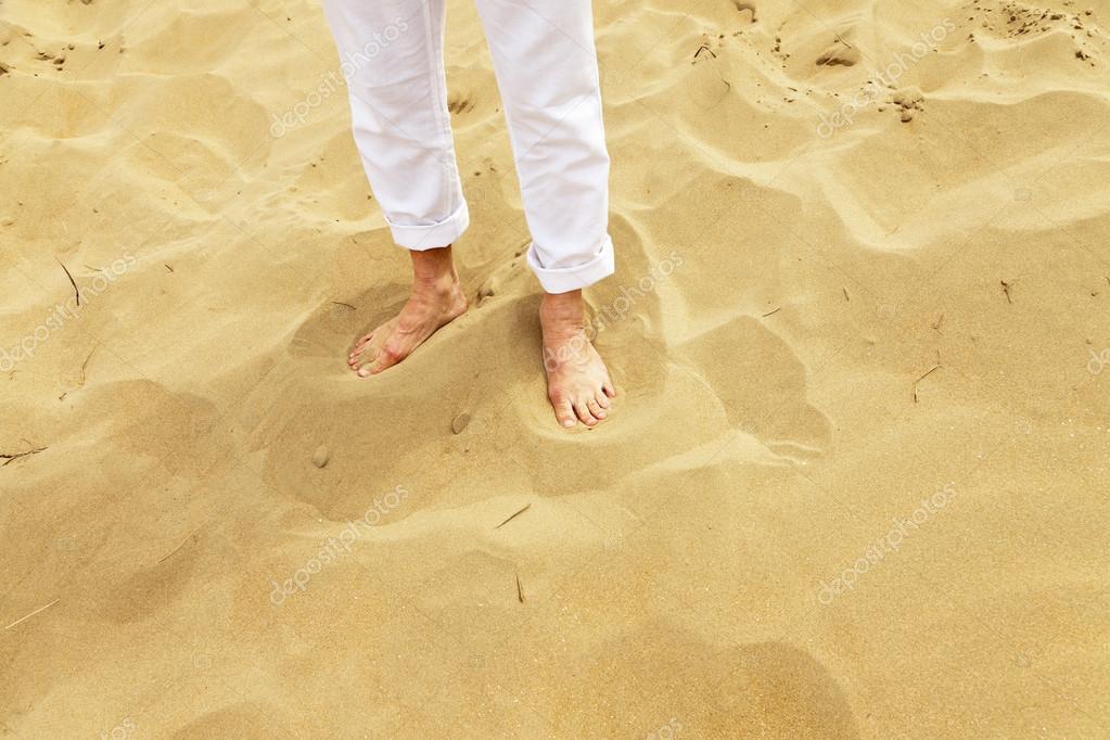 Feet of senior man standing in sand. Wearing white pants.