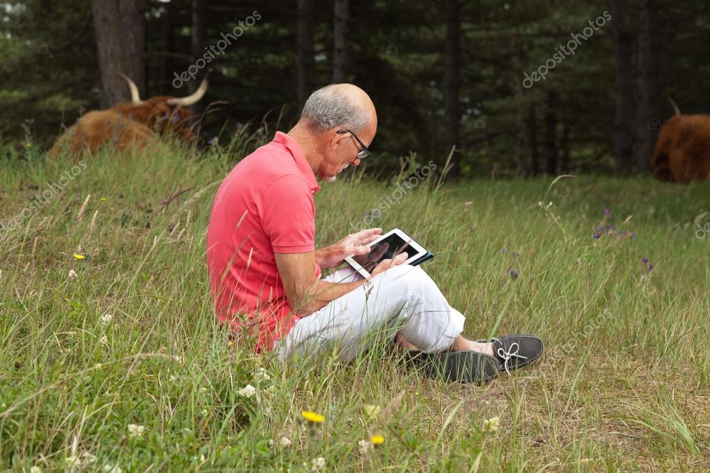 Senior retired man sitting with tablet outdoors in meadow. Scott