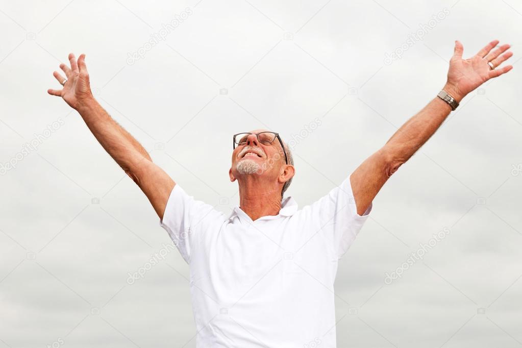 Free happy retired senior man with beard and glasses enjoying th