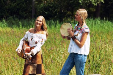 Two retro blonde 70s hippie girls making music with acoustic guitar and tambourine outdoor in nature.