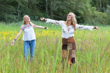 Two retro blonde 1970s hippie girls with sunglasses dancing in f