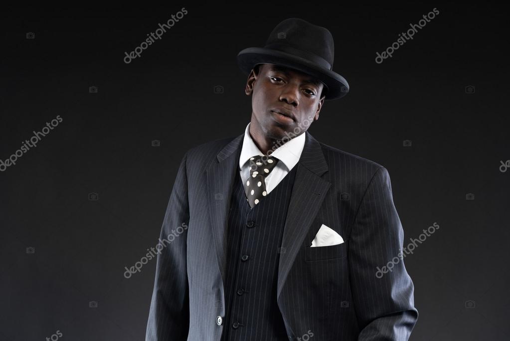 Gangster afroamericano retrò con indosso la tuta a righe e cravatta e cappello  nero. 20f037407438