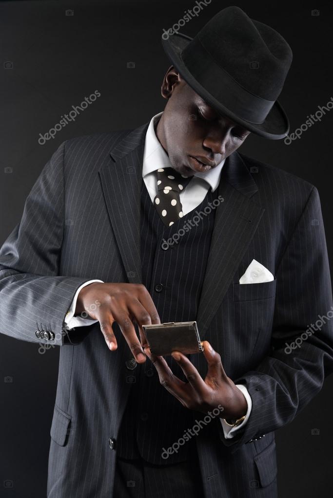 48cb811680 Retro afro-amerikai gengszter férfi csíkos öltöny és a nyakkendő és a fekete  kalapot visel. cigaretta eloszlatása ezüst színű dobozban. stúdió felvétel  ...