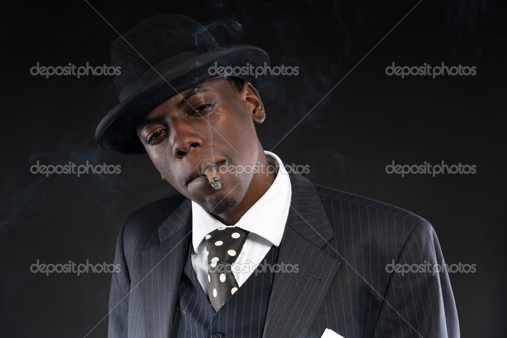 Retro african american mafia man wearing striped suit and tie and black hat.  Smoking cigar. Studio shot. — Photo by ysbrand ca5d48548b6d