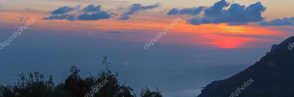 Panoramic shot of beautiful coastal sunset with cloudy sky. Corf
