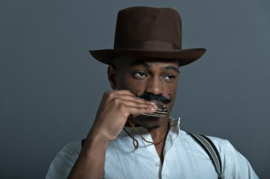 Harmonica playing retro afro america western cowboy man with mus
