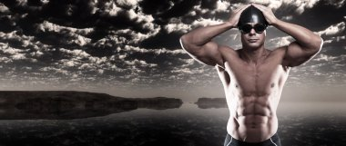 Muscled swimmer man with cap and glasses outdoor at rough sea wi