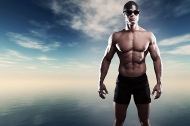 Muscled swimmer man with cap and glasses outdoor at a lake with