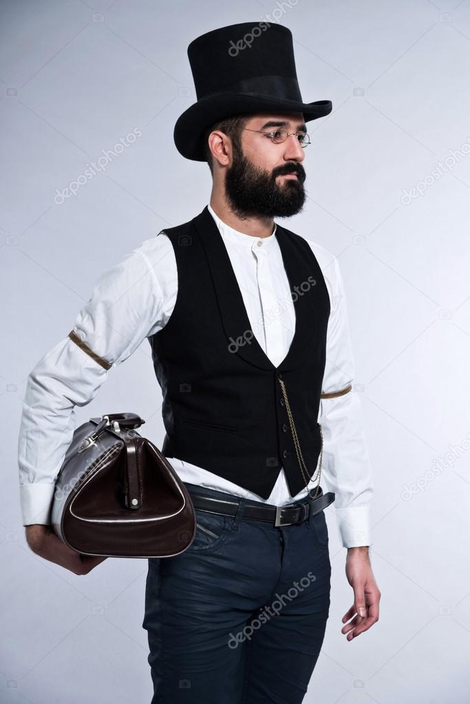 Uomo di moda retrò hipster 1900 con barba e capelli neri. indossa il  cappello nero. borsa vintage in mano. Studio shot contro grigio — Foto di  ysbrand b9bc75945137