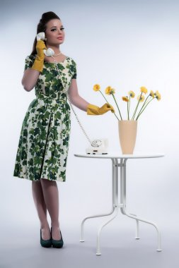 Retro 50s fashion housewife on the phone wearing yellow rubber g