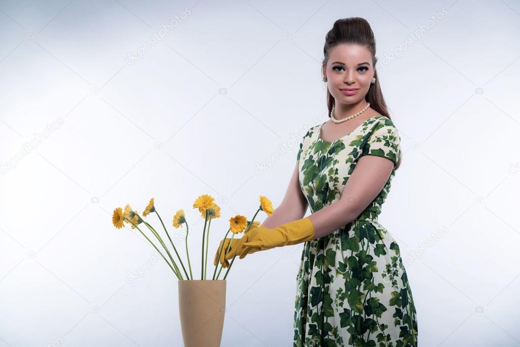 Rétro années 50 mode pour femme au foyer avec des gants de caoutchouc  jaune. mettre les fleurs dans un vase. Studio tiré contre gris — Image de  ysbrand 6fc99be7f9d6