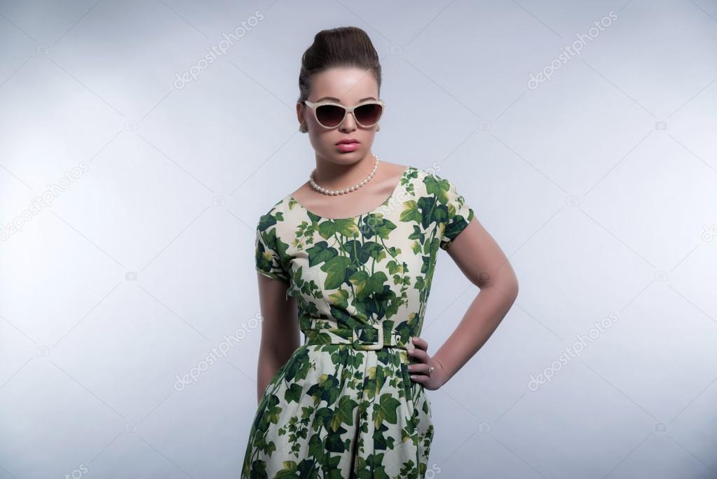 Rétro années 50 de mode jeune fille brune avec des lunettes de soleil  portant robe vert et blanc collier de perles. Studio tiré contre gris —  Image de ... 820289dd8fc3