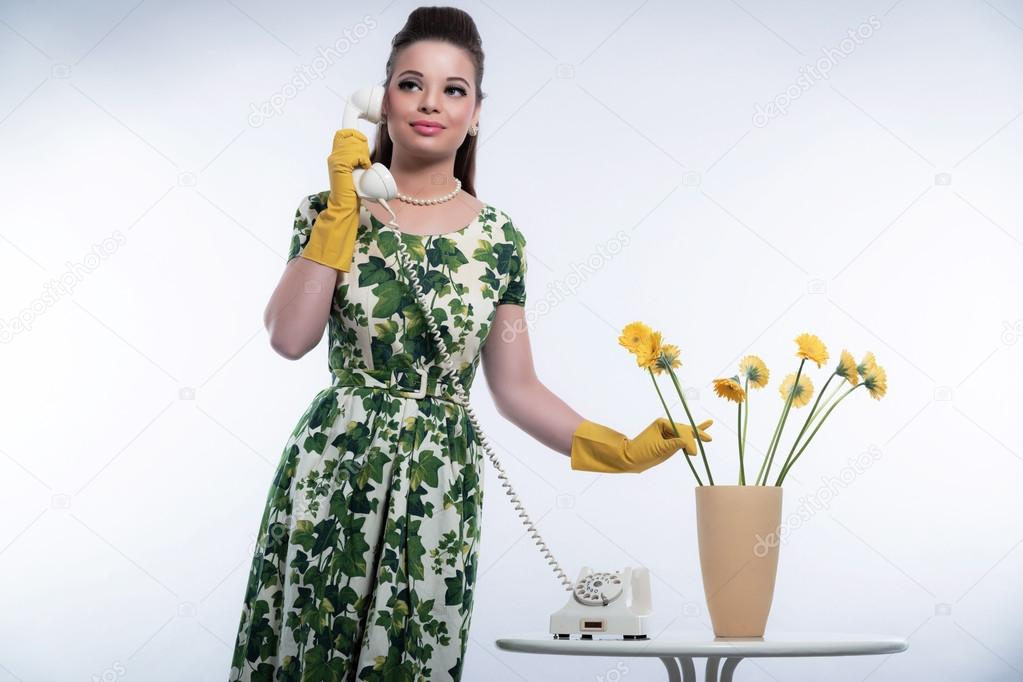 Rétro années 50 mode pour femme au foyer sur le téléphone avec des gants de  caoutchouc jaune. mettre les fleurs dans un vase. 040c5d7666df