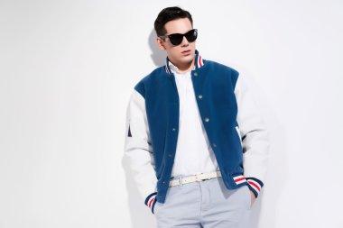 Retro fifties sportive fashion man wearing blue baseball jacket and dark sunglasses. Studio shot against white. stock vector