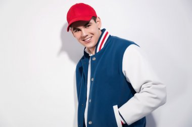 Smiling retro fifties sportive fashion man wearing blue baseball jacket and red cap. Studio shot against white. stock vector