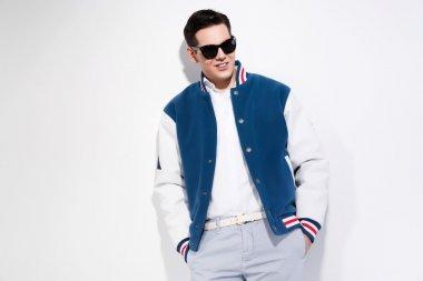 Smiling retro fifties sportive fashion man wearing blue baseball jacket and dark sunglasses. Studio shot against white. stock vector