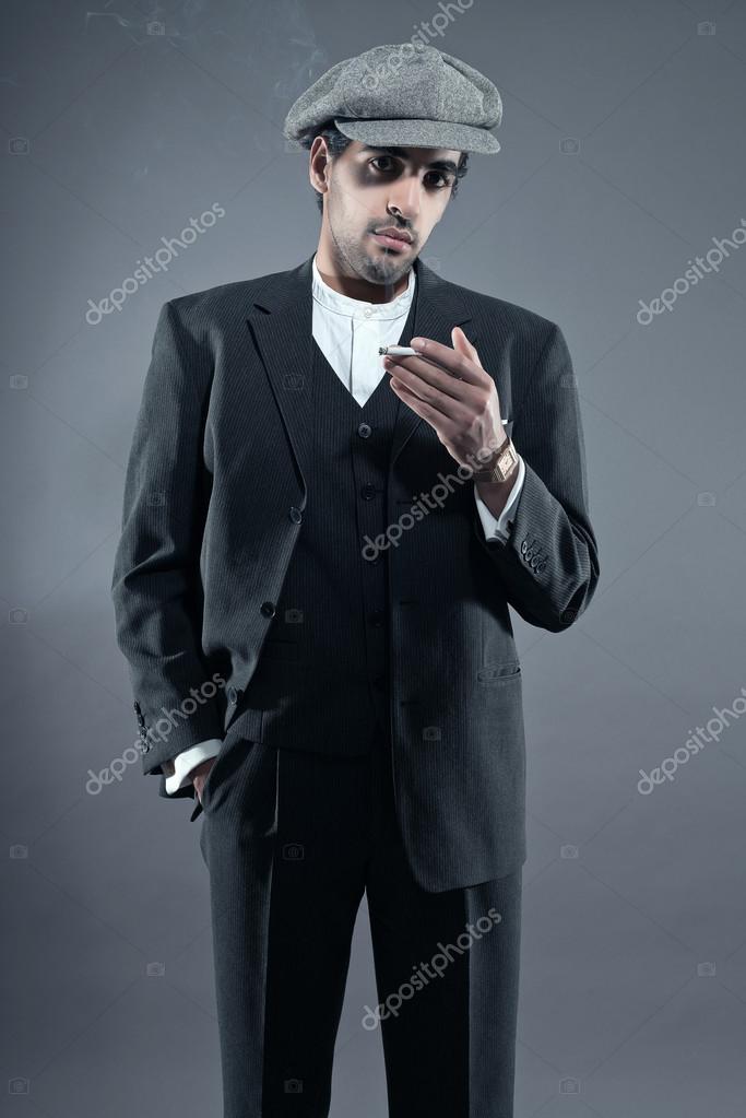 Mafie módní muž na sobě šedý proužkovaný oblek s víčkem. kouření ci– stock  obrázky d63c9b8475