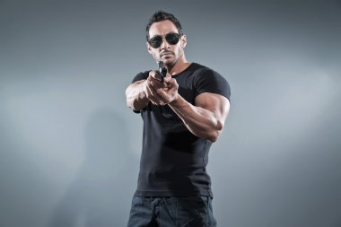 Action hero muscled man shooting with gun. Wearing black t-shirt