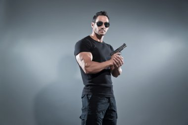 Action hero muscled man holding a gun. Wearing black t-shirt wit