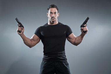 Action hero muscled man holding two guns. Wearing black t-shirt