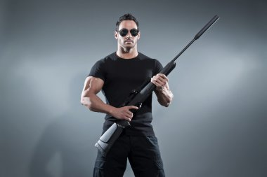 Action hero muscled man holding a rifle. Wearing black t-shirt w