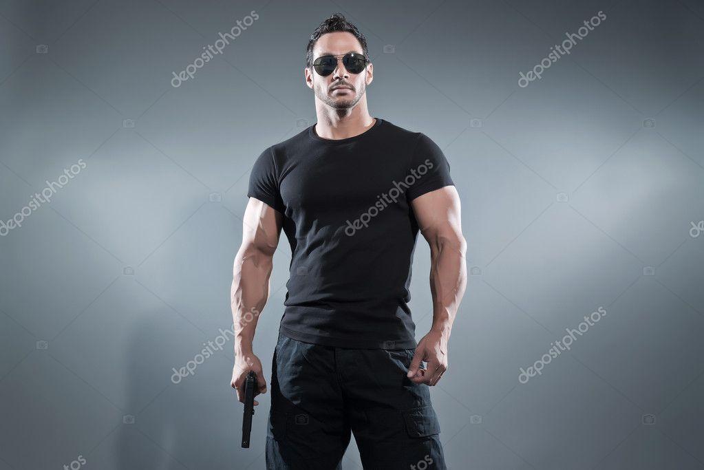 Action hero muscled man holding a gun. Wearing black t-shirt wit