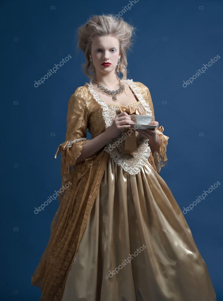 retro-barock-mode frau in goldenem kleid. in der hand eine