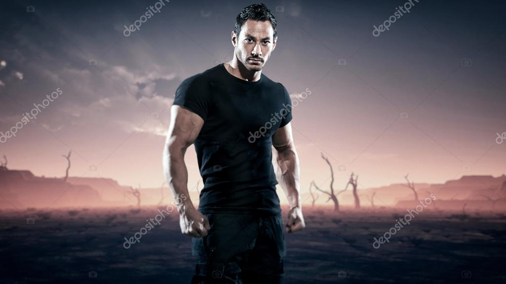 Strong muscled hero fitness man standing in desolate landscape w