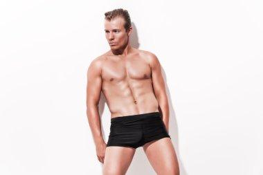 Male muscled underwear model wearing black shorts. Blonde hair.