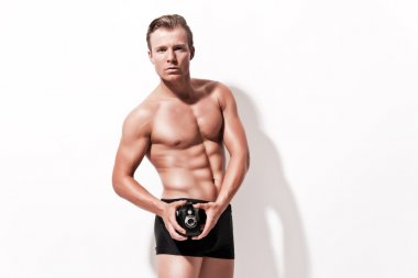 Male fitness underwear model with vintage photo camera. Wearing