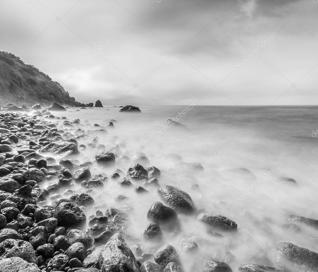 Minimalist seascape. Long exposure of sea and rocks. Black and white.