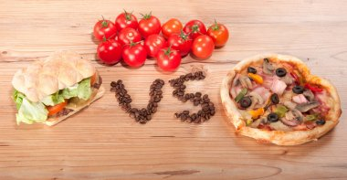tasty hamburger and pizza. vesrsus. vs. and some tomatoes
